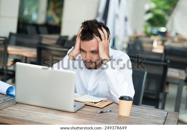 Stressed businessman sitting in front of laptop in the cafe