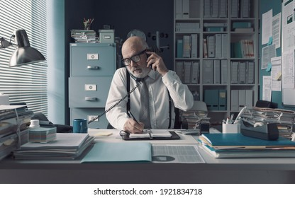 Stressed businessman sitting at office desk and answering many phone calls at the same time, he is writing down notes on a notebook