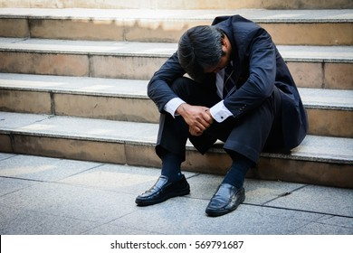 Stressed businessman sitting at stairway outdoor.Bankrupt businessman sitting outdoor.