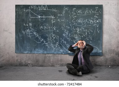 Stressed businessman suffering from headache with blackboard on the background