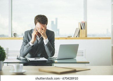 Stressed businessman talking on the phone at workplace with laptop, coffee cup and other items on desk. Blurry city view in the background