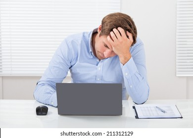 Stressed businessman using laptop while leaning on desk in office