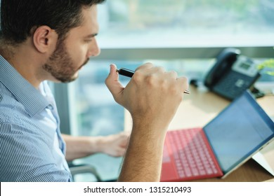 Stressed businessman working with laptop computer in office. Anxious Hispanic man under deadline at work with pc, clicking on pen for time pressure