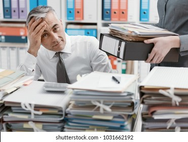 Stressed businessman working at office desk and overloaded with work, the desktop is covered with paperwork, his secretary is bringing more files
