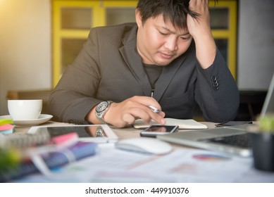 Stressed businessman Worried businessman in dark suit sitting at office desk full with books and papers being overloaded with work.