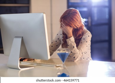 Stressed businesswoman at desk in creative office
