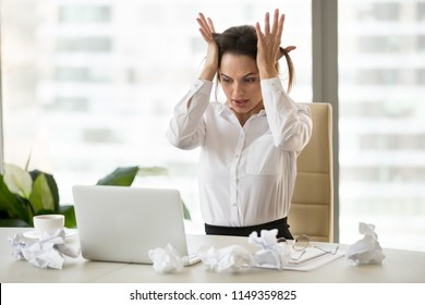 Stressed businesswoman feel despair sitting at desk with crumpled papers, unable to finish work or financial report till deadline