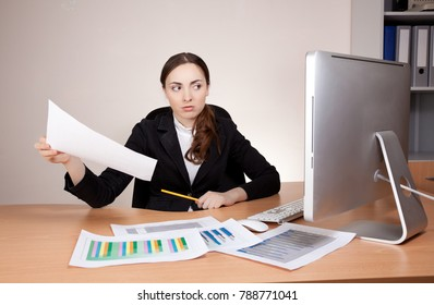 Stressed businesswoman with financial report at office