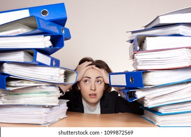Stressed businesswoman with a lot of folders on the table at office