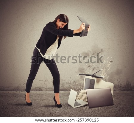 Stressed businesswoman furiously attacking computers and laptops