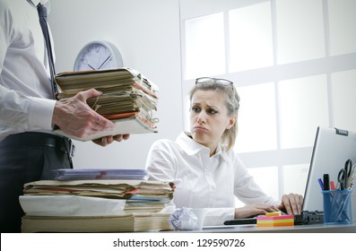 Stressed businesswoman with a too much paperwork and documents