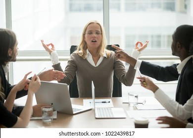 Stressed businesswoman practicing yoga at stressful work, executive woman boss meditating at meeting with diverse employees for keeping mental health and emotional balance, no stress free relief
