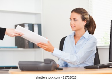 stressed businesswoman receiving a pile of paper in her office