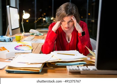Stressed businesswoman sitting in front of computer in the office