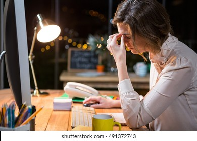 Stressed businesswoman sitting at her desk in the office