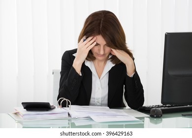 Stressed Businesswoman Sitting In Office With Financial Report