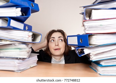 Stressed businesswoman with stack of folders at office