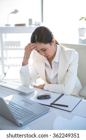 Stressed businesswoman working at her desk in work