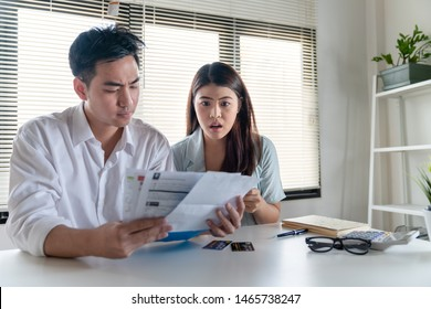 Stressed couple young family husband and wife looking so many expenses bills such as electricity bill,water bill,internet bill,cell phone bill and credit card bill in his hand no money to pay debt