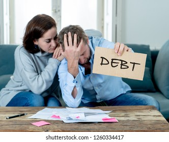Stressed and depressed young couple having many debts in accounting home finance paying bills mortgage bank statements and expenses feeling desperate in bad financial situation and bankruptcy.