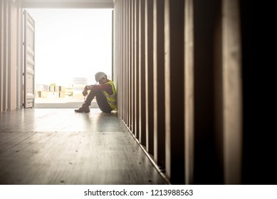 Stressed despair staff in logistic business sittng in container box at shipyard