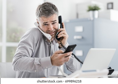 Stressed desperate businessman working in his office and having multiple calls, he is holding two handsets and a mobile phone, business management concept