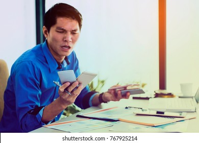 Stressed desperate businessman working in his office while there are many callers in his cellphone. business management concept