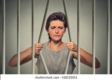 Stressed desperate sad woman bending bars of her prison cell isolated on grey wall background. Life limitations, law violation consequences concept. Face expression emotion