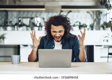 Stressed and disappointed young man freelancer looking at his laptop, got bad news