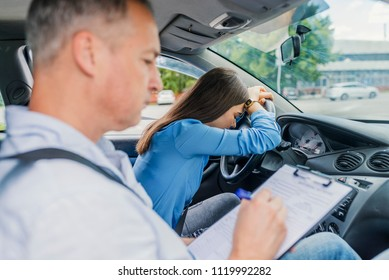 Stressed and disappointed young woman failed on driving test. Instructor of driving school giving exam while sitting in car. Woman getting a driving lesson in the car