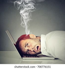 Stressed employee man with overheated brain using laptop