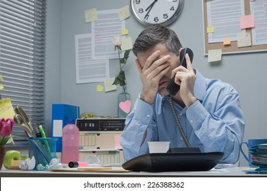 Stressed employee on the phone touching his forehead.