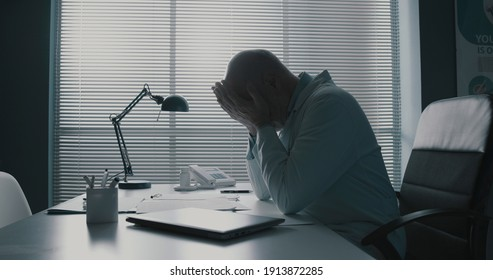 Stressed exhausted doctor sitting at office desk and resting with head in hands, burnout in healthcare concept