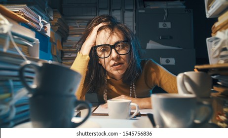 Stressed exhausted woman sitting at office desk and working overtime, she is overloaded with work