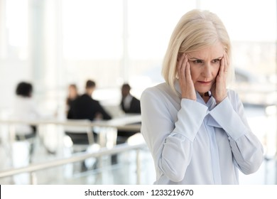 Stressed fatigued mature businesswoman touching temples suffer from headache migraine at office meeting, tired exhausted old woman employee feels dizzy at work, climax and hormone imbalance concept