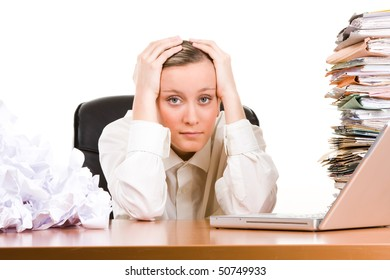 A stressed female executive with her head in her hands, sitting at her desk covered a pile of papers and stack of files.