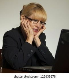Stressed female executive office with hands on face looking at computer