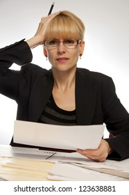 Stressed female executive office with papers with pen in hand