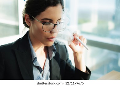 Stressed female executive vaping at work while using her laptop computer. Concept of Smoking Cessation Attractive young businesswoman using a vaping device for nicotine addiction withdrawal symptoms.