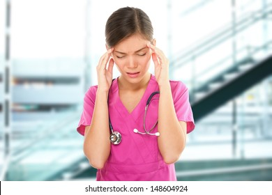 Stressed female nurse medical professional with headache. Portrait of woman nurse having migraine pain being overworked having stress at health care hospital.