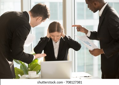 Stressed female office worker closing ears with hands while sitting at desk surrounded by nervous mad colleagues or bosses pointing at mistakes in report, demanding do job faster. Criticism at work