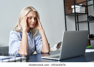 Stressed forgetful old middle aged business woman suffering from headache after computer work. Tired upset 50s lady massaging head feeling stress, fatigue or migraine using laptop at home office.