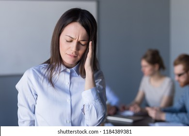 Stressed frustrated business woman touching temple feeling strong headache or suffering from chronic migraine during stressful office meeting tired of difficult job, problems or hormone imbalance