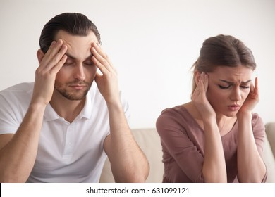 Stressed frustrated couple touching head with eyes closed, feeling strong headache or tired of arguing, exhausted man and woman trying to concentrate, lack of sleep result, hangover effect, bad day