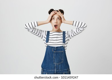 Stressed frustrated dark-haired young female with two hairbuns dressed in denim clothes holds hands on head, keeps mouth opened in despair, doesn`t know what to do in stressful situation, feels lost