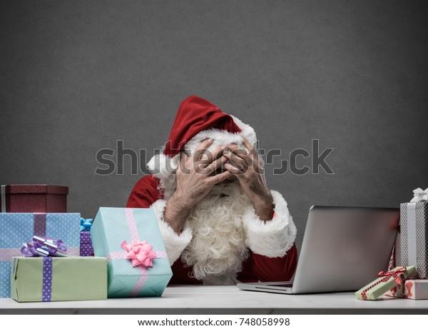 Stresst frustrierten Weihnachtsmann mit Kopf in den Händen, der mit seinem Laptop verbunden ist, er hat Computerprobleme am Heiligabend