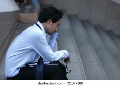 Stressed frustrated young Asian business man sitting on stairway. He feeling disappointed or tired with job.