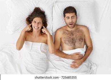 Stressed frustrated young European female grimacing, suffering form insomnia, plugging ears with fingers because of her drunk bearded husband who is snoring loudly, lying in white bed next to her