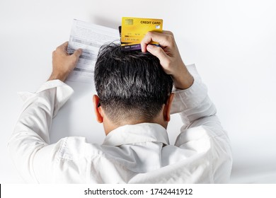 Stressed gray haired man wear white wrinkled shirt holding credit card and scratch the head worried debt, bills bank statement,feeling desperate in bad financial situation and bankruptcy