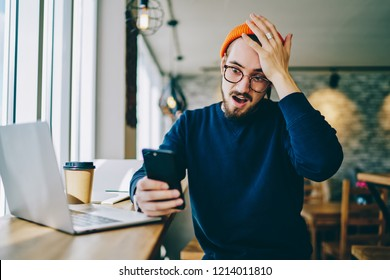 Stressed hipster guy in spectacles shocked with bad news get on smartphone during remote job in coworking office, male student open mouse disappointed with mobile phone failure and problems with devic